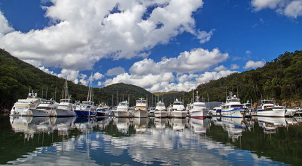 Luxury cruisers rest in their berths in Bobbin Head Marina on the Hawkesbury River. The marina is situated in the Kuring-gai Chase national park.