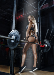 Beautiful athletic girl at workout in fitness gym. Art photo.