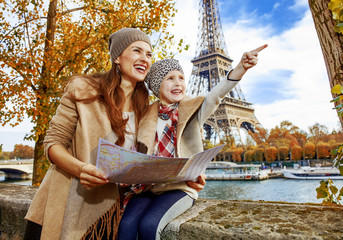 mother and daughter tourists in Paris holding map and pointing