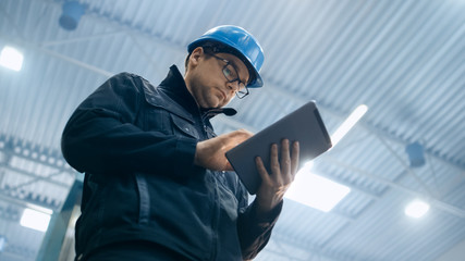 Factory worker in a hard hat is using a tablet computer.