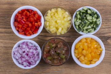 Assortment of vegetables sliced. Peppers, tomatoes, cucumber and onion in bowls