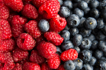 Close-up on composition of raspberry and blueberry fruits