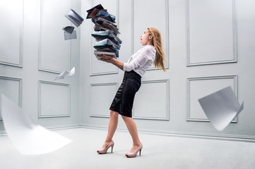 Fototapeta Business woman carrying a pile of papers. Conception of overwork and paper work obraz