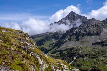 Begrünter Fels vor einem Wolkenverhangenen Bergipfel