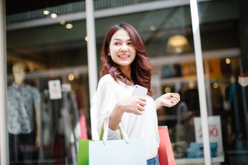 happiness, consumerism, sale and people concept - smiling young Asia woman with shopping bags at outdoor shopping mall