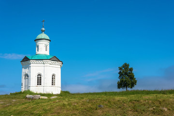 A small chapel on the background of blue sky.