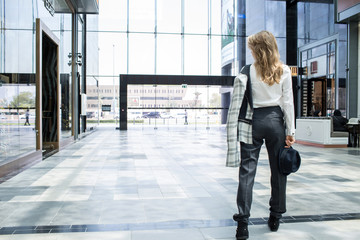 Young and slim woman holding her hat in grey jacket is walking away in the lobby of a modern building
