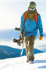 Close up shot of a snowboarder in helmet walking at the top of a mountain with his snowboard in hand