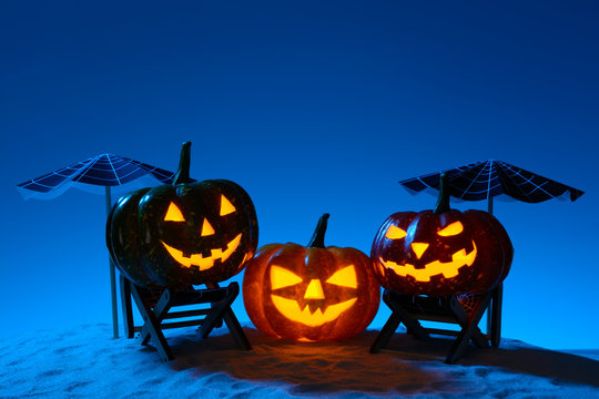 Carved pumpkins in composition on sand