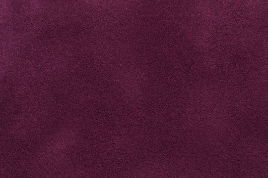 Background of dark purple suede fabric closeup. Velvet matt texture of wine nubuck textile