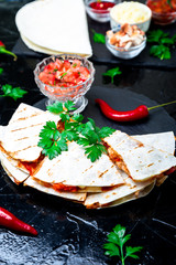 Mexican quesadilla with salsa sauce on black slate stone plate. Chili pepper.