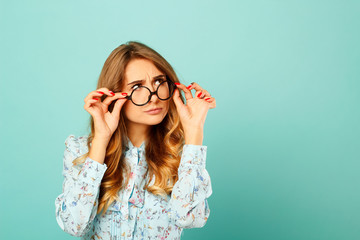 Pretty thoughtful girl wearing glasses over blue background Wall mural