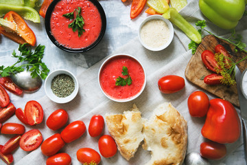 Composition of gazpacho and fresh vegetables, bread, serving a family dinner, top view