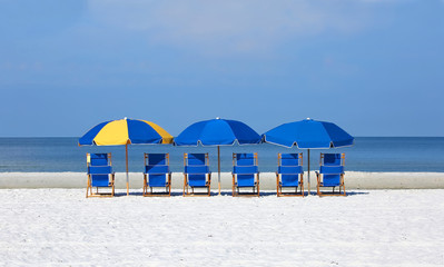 Beach chairs and umbrellas lined up in front of the blue waters of the Gulf of Mexico in Fort Myers Beach, Florida, USA.