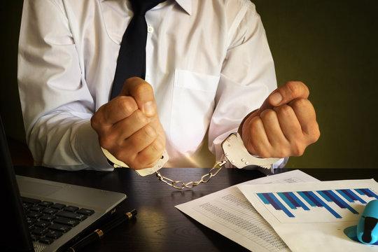 Businessman in handcuffs. White collar crime concept.
