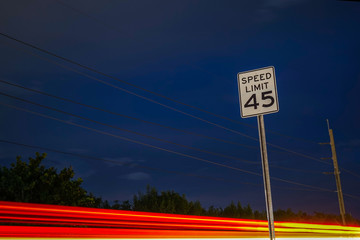 Light Trails Past a Speed Limit Sign