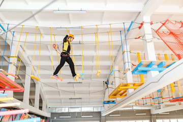 Young man climb with rope belay and helmet at indoors amusement rope park
