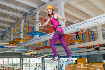 Young woman walking on a ladder in rope park gym indoors