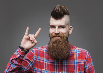 Young trendy man making rock gesture