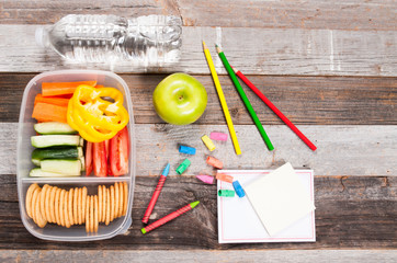 School supplies and lunch on wooden background.