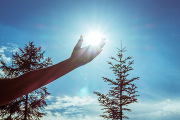 women hand is holding the sun