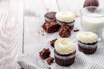 Chocolate cupcake with buttercream on white wooden background whith milk cup