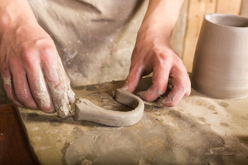 potter, stoneware, ceramics art concept - craftsman fingers forming the handle from raw fireclay, master hands working with some piece of clay, male stand at a workshop near the table