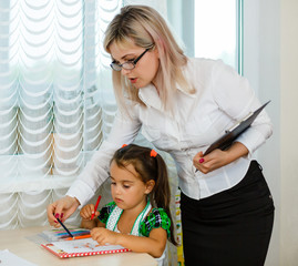 Mother looking how her child daughter drawing a picture