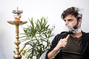 Young man smoking hookah