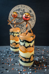 Autumn Halloween parfait with smiling pumpkins and moon