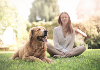 Girl sitting in the grass with her dog