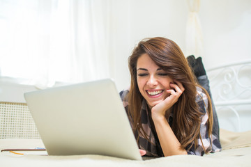Smiling young woman using laptop while lying on bed at home.
