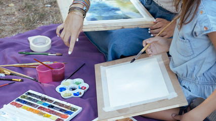 A lesson in drawing of watercolor paints for young girl on the nature at park