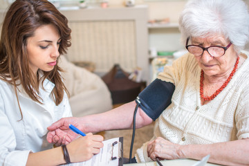Nurse measuring blood pressure of senior woman at home. Female doctor writing medical results to clipboard.