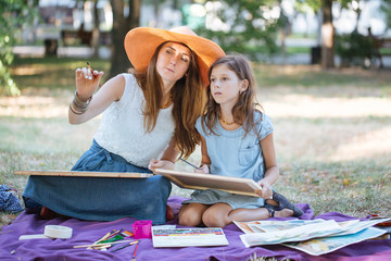 Woman with daughter drawing by watercolor paints at the park