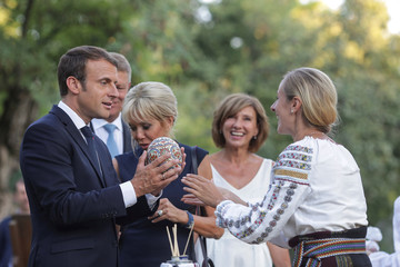 French President Emmanuel Macron reacts after receiving a painted ostrich egg during a visit at the Village Museum in Bucharest, on the French President's three day tour of central and eastern Europe, in Bucharest