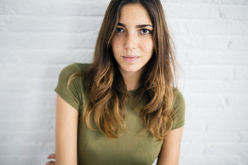 Portrait of a pretty woman against a white brick wall