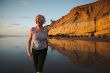 Active senior woman on beach at sunset
