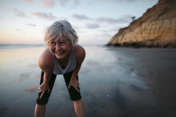 Vibrant mature woman enjoying herself on the beach at sunset