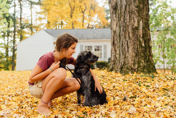 teen and her dog in yellow leaves