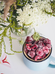 Wildflowers and frozen raspberries on a white table