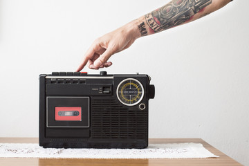 Tattooed arm pushing play button of tape recorder
