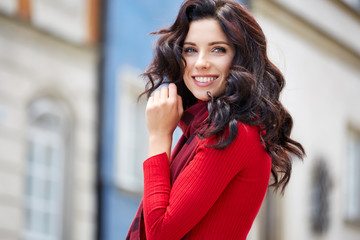 Beautiful woman in a red autumn sweater on the street.
