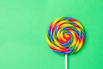 Tasty appetizing Party Accessory Sweet Swirl Candy Lollypop on Green Background Top View