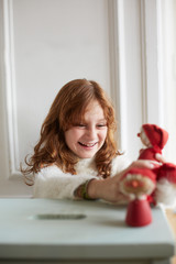 Little girl playing with figures of christmas dwarfs