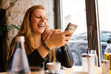 Smiling woman using a mobile phone while sitting in cafe
