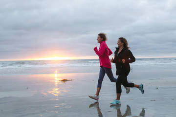 Two woman friends enjoying a walk together on the beach at sunse