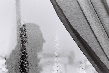 Silhouette of a man through a wet window, black and white