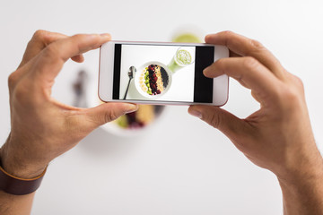 man photographing healthy breakfast by smartphone
