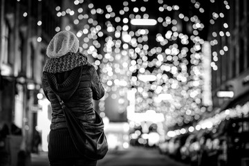 Girl at christmas shopping with bokeh lights in background